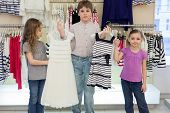The boy helps cute girls to choose dress in shop of childrens clothing