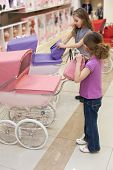 image of buggy  - Two girls in a toy store with a rows of dolls purchased a handbag and buggy - JPG