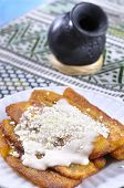 picture of plantain  - Stack of fried plantain bananas with cream and cheese on plate with attractive traditional Mexican background - JPG