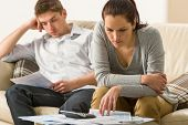 stock photo of annoyance  - Annoyed couple calculating their finances during recession - JPG
