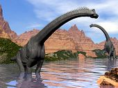 pic of herbivore animal  - Two brachiosaurus dinosaurs in water next to red rock mountains by beautiful day - JPG