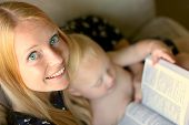 Woman Reading Book While While Holding Baby