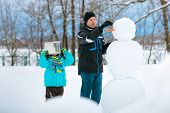 Little boy with his father making a snowman
