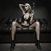 picture of smoking woman  - Sexy blonde woman smoking on sofa in dark - JPG