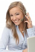 Happy blonde dispatcher working, using headphones, smiling.