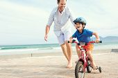 stock photo of children beach  - Father and son learning to ride a bicycle at the beach having fun together - JPG