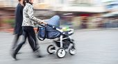 Young Family With Small Children And A Pram Walking Down The Street