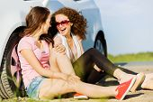 Young pretty women sitting near white car at side of road