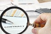 Magnifying Glass Over Contract Papers