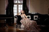 Luxury young smiling beautiful woman in vintage dress in elegant interior.