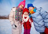 Joyful kids in winterwear looking at camera while having happy time outside