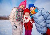 Joyful kids in winterwear looking at camera while having happy time outside