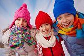 Joyful kids in winterwear looking at camera with smiles outside