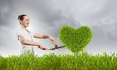 foto of grass-cutter  - Young happy businesswoman cutting bush with grass cutter - JPG