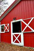 stock photo of silos  - Large red barn with an open half door - JPG