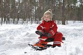 In Winter, In The Forest Boy Is Sitting On A Sled And Smiling.