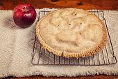 Homemade apple pie cooling on a wire baking rack and sitting beside a cortland apple.