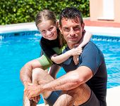 cute little girl with her father in a wetsuit near the pool in the summer