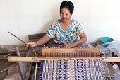 Thai woman weaving traditional straw mat using Cyperus alternifolius stems, Khon Kaen, Thailand