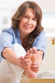 stock photo of home remedy  - Beautiful woman doing feet reflexology or zone therapy at home - JPG