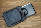 picture of tilt  - Overhead tilted view of laptop computer personal weapon and carry case on rustic wooden boards - JPG
