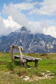 Wooden Bench And In The Background The Austrian Alps