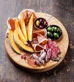 Antipasto Snack Ham, Melon And Olives On Wooden Background