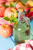 stock photo of vinegar  - Homemade Vinegar galas apples on a table in a farmhouse - JPG