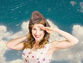 stock photo of ww2  - Old fashion portrait of a pretty female pin up model wearing retro style pilot cap while saluting on textured ww2 sky. Call to arms ** Note: Soft Focus at 100%, best at smaller sizes - JPG