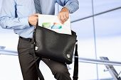 Businessman Holding And Geting Out   Documents With Graphs  From His   Leather Briefcase.