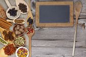 Spices On Rustic Wooden Board With Chalkboard