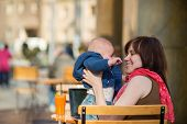 Happy Young Mother With Her Little Son In A Cafe