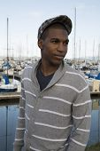 Black Male Model Wearing Sweater And Newsboy Hat At Waterfront