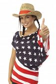 Portrait of happy American girl showing ok sign, wearing American flag t-shirt and straw hat.