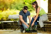 Young man helping his girlfriends to put rollerblades