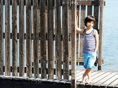 pic of dock a pond  - Little kid walking down the bridge on a sea summer dock - JPG