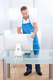 image of disinfection  - Handsome young janitor or cleaner cleaning an office spraying the top of the desk with disinfectant before the office workers start their day - JPG