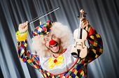 Funny clown plyaing violin against curtain