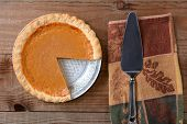 High angle shot of a pumpkin pie that has been cut into. Shot on a rustic wood table with a Autumn themed napkin and server by its side. Horizontal format.