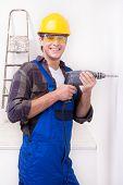 Smiling repairman using drill