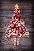 image of hazelnut tree  - Christmas tree made of hazelnuts with red baubles and gifts on wooden background - JPG