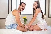 Young couple smiling at camera in bed at home in bedroom