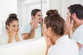 Young couple putting on face cream at home in the bathroom