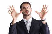 Serious businessman with finger spread out on white background