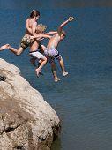Adventurous Boys Jumping into Lake