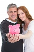 Casual couple showing their piggy bank on white background