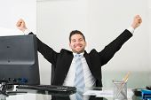 Successful Businessman With Arms Raised At Desk