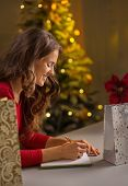 Happy Young Woman Writing In Notebook List Of Christmas Purchasi