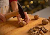 Closeup On Young Housewife Chopping Walnuts