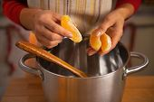 Closeup On Young Woman Putting Orange Slices Into Pan